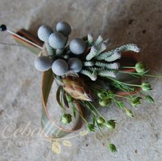 The groomsmen's boutonnieres will be silver brunia and green sage wrapped in dusty blue ribbon all the way to the ends of the stems,