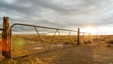 Stock Footage of A beautiful static timelapse after a storm with a drenched Karoo landscape of an old rusted gate and fence with puddles of water while the sun dips through the clouds with an intense golden glow. Explore similar videos at Adobe Stock Stock Video, Windmill, Geology, Stock Footage, South Africa, Fence, Gate, Dips, Adobe