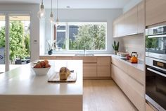 Alternate view of kitchen which shows custom millwork and continuous wood backsplash which creates an effortlessly seamless effect.