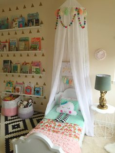 Interior design by Maya Ostrander. Bed canopy, cloud pillow, plush, custom toddler bedding, bunny lamp (PB Teen), side table (Hobby Lobby), Ikea rug, weaved baskets, book ledges, kids books.