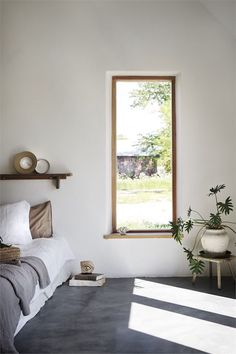 my scandinavian home: A Striking Holiday Home on The Swedish Island Of Gotland - bedroom with concrete floor, white walls and wood framed windows.