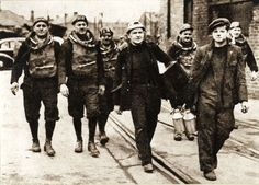 Photograph of six members of the Shotton Mining Rescue Team walking near the colliery buildings over waggon lines, while assisting in the rescue of the victims of the disaster in 1951; five men are wearing breathing equipment and helmets; one man is wearing a helmet and carrying a large box; the sixth, a young boy, is wearing overalls and carrying cans