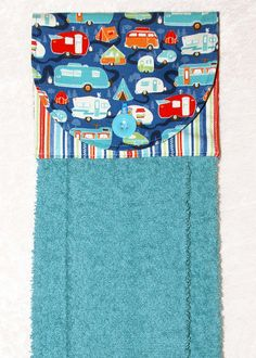 A blue hand towel with cheerful campers and stripes. The plush blue towel is more luxurious than a standard kitchen towel. Featuring a designer fabric of travel trailers on blue and a coordinating blue stripe fabric, it is sure to add fun to your home or camper kitchen and bath.  This handmade hanging towel works well buttoned over the handle of stove or dishwasher. It can even be used over a towel bar in the bathroom or powder room.  6 x 17 when hanging. The front of this hanging towel…