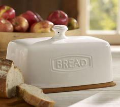 """A handsome way to keep loaves of bread fresh, our Rhodes Bread Box features a ceramic lid that fits over a cutting-board base.        Overall: 12.5"""" long x 7"""" wide x 7.5"""" high      Lid made of glazed stoneware.      Base is stained mango wood.      Catalog / Internet only."""