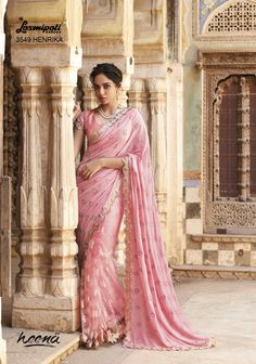 Rosy Pink gerogette half and half jacquard net saree with bordered jari lace and jari work on the fall added satin silk inner and smoky pink brocade blouse.