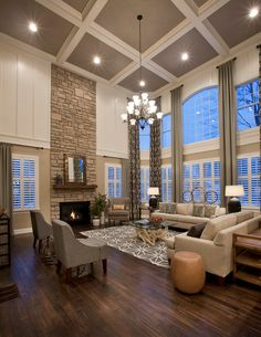 Large living room with coffered ceiling, stone fireplace, dark wood floors, floor to ceiling curtains, patterned area rug, large chandelier | Mary Cook