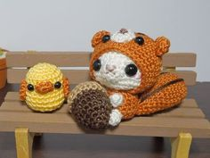 amigurumis a kitty, dressed as a squirrel, eating an acron, with a duck!