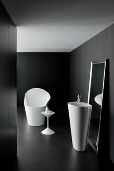 """Laufen Palomba Floor Standing Menhir Vessel. From the soothing contours of the ocean come the soft ripples of Laufen's Palomba Menhir vessel. The floor-standing ceramic washbasin's beautiful curves are reminiscent of a tide-swept rock that organically morphs the towers into the basin surface. Distinguished by a clean white finish, Menhir (which means """"tall stone"""" in Breton) makes any bath feel a mere stone's throw from the surf."""