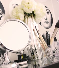 Vanity with Diptyque candle and Fornasetti wallpaper