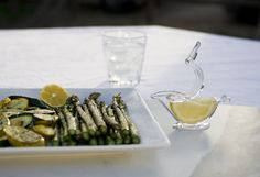 A Press Art lemon squeezer on the table with a plate of Asparagus.