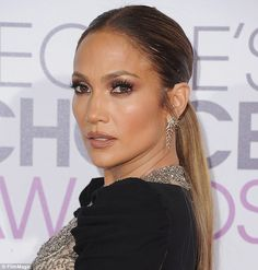 Singer/Actress Jennifer Lopez wore a Reem Acra Pre-Fall 2017 gown with a sheer beaded bodice and carried a Ferragamo clutch. Make-up artist, Mary Phillips, layered three different L'Oreal foundation shades 'for sexy, healthy 3-D skin' | People's Choice Awards 2017 at Microsoft Theater, Los Angeles, California. Jan 18, 2017