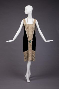 Dress 1926-1927  Straight Long Waisted Black Silk Velvet Dress With Built In Slip Of Beige Silk Crepe Satin Showing At Slit In Front That Goes From Hem To Hip. Cream Lace Insert At Low V-Neck With Large Ornament At Top Of Slit. Ornament Is Silver, Pear, Jade and Rhinestone That Connects With Pearls and Green Glass Beads That Go Around The Neck. Cream Lace Extends From Ornament To From Loop In Back.  The Goldstein Museum of Design