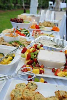 Outdoor wedding buffet... white, silver, clear glass. The food is the color.