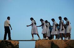 Colegialas caminando sobre una tabla en Sri Lanka