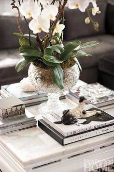 Floral centerpiece flanked on four sides with books and interesting object resting on each. Find Your Look | New England Home Magazine