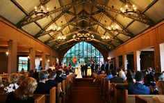 Presidio: A photo of a wedding ceremony inside Chapel of Our Lady on the Main Post. The chapel has an ornate ceiling with chandelier lighting and the wall behind the altar is glass.
