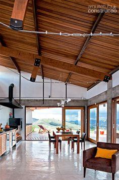 Cozinha de estar: aberta, ela se confunde com o deck e a sala. Integrados, os ambientes viram uma área social única, imersa na paisagem. O vão grande, de 6 m, pediu estrutura de vigas vagão, amparadas por tirantes de aço.