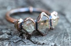 This quartz crystal ring is gorgeously organic and rustic. It features five herkimer diamond crystal points inside of copper. These herkimer diamonds are a peach and lemon color. They shine white and pinkish. It is like something worn by an ancient tribal queen! I created the ring with a technique called electroforming. Copper is deposited over the stone over 12-24 hours using electrical currents. It creates a gorgeously organic and hefty piece with a setting that looks like animal skin or…