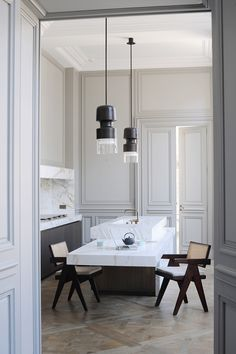 In the kitchen, all technical elements are hidden behind calacatta marble partitions. Bronze 'Fingi' suspension lighting by Eric Schmitt (Eric Schmitt). Office armchairs by Pierre Jeanneret (Galerie 54). Photo © Adrien Dirand. http://www.yatzer.com/joseph-dirand-saint-germain-paris