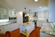 Kitchen remodel with wine rack in island, granite countertops, white cabinets with glass inset doors, kitchen hood vent.