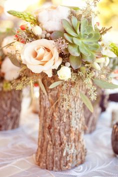 Tree stump center pieces.  I like the tree stump but with different flowers.
