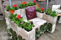 Crazy, awesome cinderblock chair decked out with flowers. Whadda garden feature! Milner Village Garden Centre in Langley, BC Canada featured on Funky Junk Interiors
