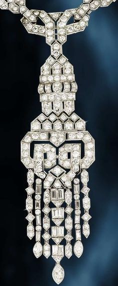 An art deco diamond necklace, circa 1930.   Of pierced geometric design, set throughout with old brilliant, brilliant, single, baguette and marquise-cut diamonds, the front formed of six crenelated plaques, suspending a large detachable brooch/pendant of similar design, terminating in seven graduated tassels, on a detachable single-row backchain of hexagonal and lozenge-shaped links, diamonds approximately 23.90 carats total.