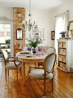 Exposed brick and hardwood floors make this farmhouse dining room inviting.