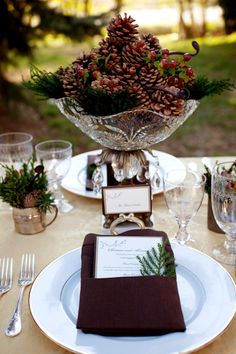 Simple pinecones accented with berries and branches in a crystal bowl make a fabulous centerpiece for a Christmas themed vow renewal    winter-wedding-decor-pinecone-centerpiece