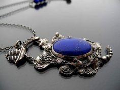 Laguna Lapis lazuli oprawiony w srebrną ramę bardzo bogatą w szczegółowe zdobienia: małe rybki (3), płaszczkę, rozgwiazdy (2), muszelki, wodorosty, statek i inne. Iwona Tamborska