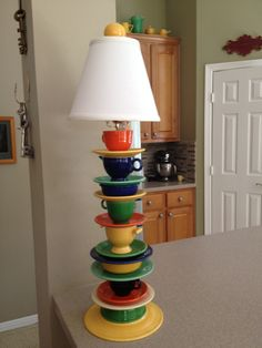 """Collected Fiestaware from estate sales and antique stores until I had enough... My awesome hubby drilled a 3/8"""" hole in every piece with a diamond bit.  Put it all together with a lamp rod and socket kit from Lowe's (and go on a mission for the perfect shade!).  PS, the finial is a salt shaker rigged with epoxy and a screw so it would thread to the harp.  Really adds to my Fiestaware kitchen, huh!?  :-)"""