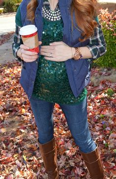 Layers done right. A sequin top over a rolled up sleeve flannel shirt, vest, jeans, and boots.