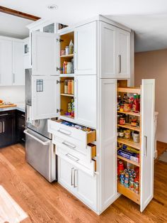A custom pullout pantry creates extra storage space in this contemporary kitchen. Plentiful drawers and cabinets help stow away other essentials while keeping them close at hand.