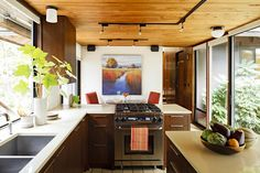 Classic mid century kitchen design features beautiful cabinet architecture and ornamental fixtures. View kitchen remodeling ideas by Mosaik Design.