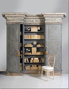 I love the idea of this piece although its details are too ornate for me. Still, the idea of two cabinets with a bookcase between and crown moulding (and base) unifying the piece is a terrific concept. It could probably be created with case good cabinets, a bookcase and crown molding.