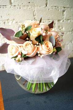 Peach rose hand-tie with snow berries and pearls, arranged in a glass fish bowl vase.