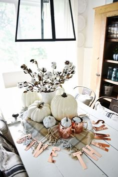 Neutral and Copper Fall Centerpiece: Love copper? Put Moscow mule mugs to good use by filling them with small white pumpkins. And instead of hanging that fall banner across your mantle, drape it around the rest of your centerpiece.