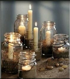 Mason jars with sand and candles. Great for a beach wedding or event