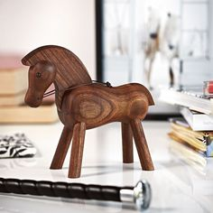 Rosendahl Kay Bojesen HorseThe walnut Kay Bojesen horse first saw the light of day in the beginning of the 1930s. With its proud stance, luxurious mane and reins at the ready, the horse invites us on an imaginary journey at a brisk gallop.Its soft curves and stiff legs give the horse the typical expression Kay Bojesen's wooden family of animals is known for: Playful contours that don't try to reflect those of real animals, but imaginative variations instead.