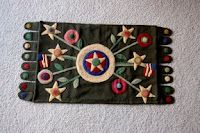 A wool penny rug that I bought as a kit at the store in Trinidad CA.  It's now in Eureka - I've heard.  Trying to mark the embroidery on wool was a challenge - light tables don't work on wool!