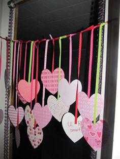 """Hung these curtains of hearts across my kids doorways for them to see the morning of valentines day.  The outside has scrapbook paper on it and the backside facing into their rooms has reason we love them written on the hearts.   I believe I got this idea from Pinterest but couldn't find the original source to acknowledge and thank.    My kids love their """"Curtains of Love""""!"""