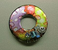 Pretty little pendant made from an ordinary zinc-plated washer! With the addition of alcohol inks, some wire, and beads, it's made awesome (from life made creations blog).