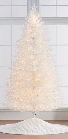 "A modern take on merriment, this translucent-white tree is also our ""greenest"" with needles constructed from recycled plastic bottles. Each glamorous branch has a tinsel-like texture, and thousands of LEDs can be switched between Warm White and Multicolor. This exclusive showpiece will create an unforgettable holiday experience."