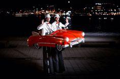 Das rote vintage Cabriolet ist illuminiert und darft deshalb auch in der Nacht gehen. Das Stelzenläufer-Kostüm ist weltweit einzigartig. Außerdem kann es sich in der Mittel teilen und gewährt dem Zuschauer so einen Einblick in das innere des roten Cabrios auf Stelzen.