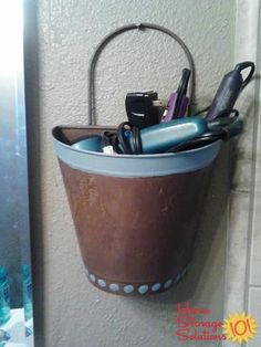 Use a heat resistant garden basket hung on your wall as a hair dryer holder, plus for other hair styling tools and appliances as well {featured on Home Storage Solutions 101, plus 9+ other hair appliance holder ideas}