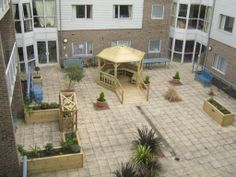 Care Home Courtyard - including gazebo with wheelchair accessible ramp and handrails, raised vegetable bed, sensory garden areas with raised garden planters planted with sensory plants and cottage style archway entrance.