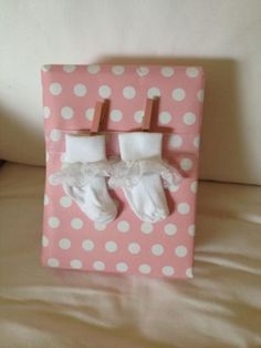 Cute way to wrap a baby shower gift with little socks and clothespins on a ribbon.