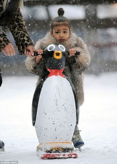Adorable: Bravely, the toddler decided she could go it alone and held on to one of the rink's large penguin skating aid while she made her way across the snow-laden ice