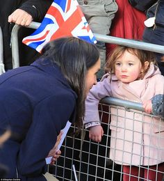 Meghan crouches down to speak to a young fan as people praised her 'down to earth attitude' on her first royal outing