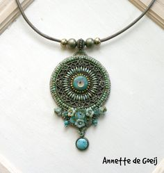 This one of a kind necklace is made with a big round metal filigree, a turquoise cabochon, turquoise beads, metal beads, metal flowers, Czech